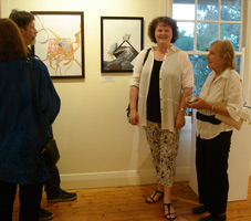 Phillips in front of two of her art works beside Rena at the opening of a BeAn art exhibition